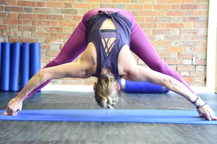 Lisa bending down in Yoga pose